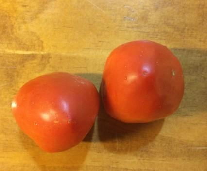 Dos tomates rojos con fondo de madera